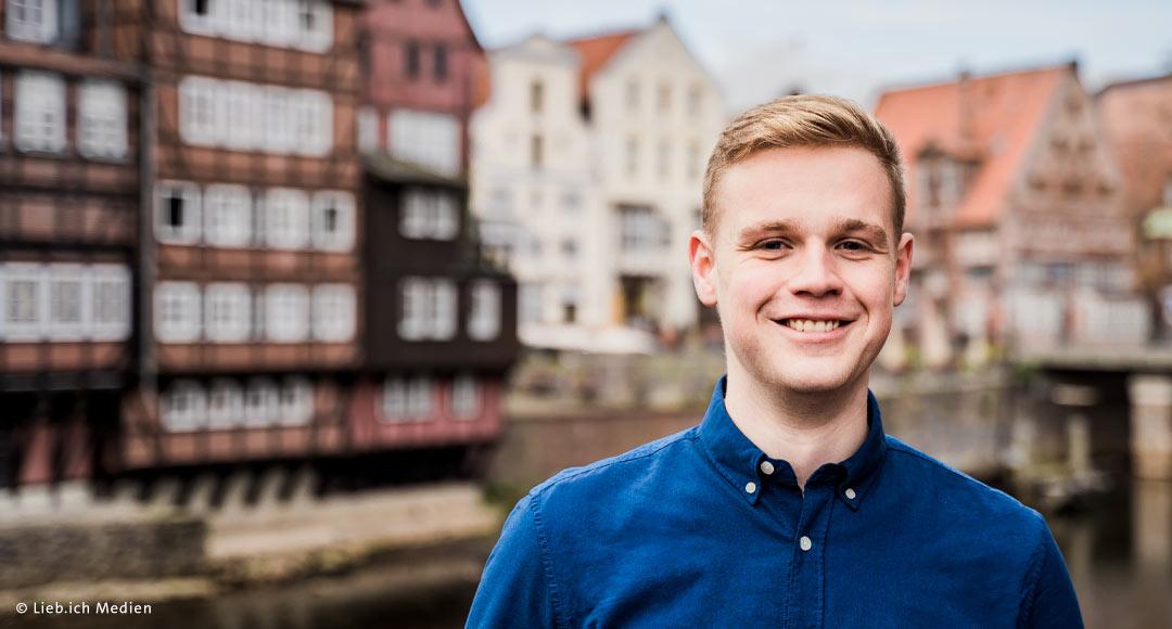 Jakob in blauem Hemd für historischer Kulisse am Stint in Lüneburg