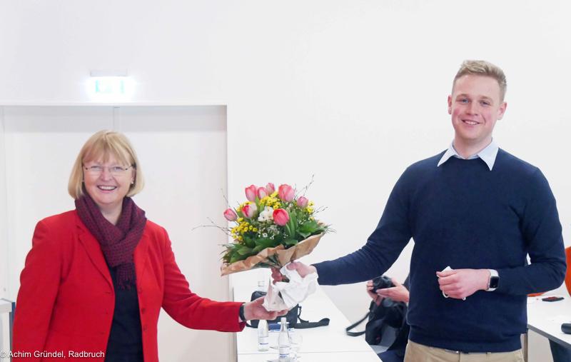 Andrea Schröder-Ehlres überreicht  Jakob Blankenburg einen Blumenstrauß